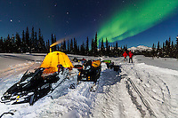 Snowmobilers camped for the night are greeted with Northern lights while traveling along the North Canol Heritage Trail, Yukon Territory, Canada.