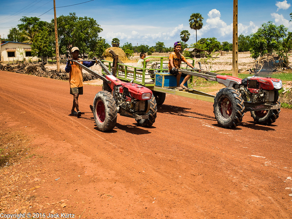 03 JUNE 2016 - SIEM REAP, CAMBODIA: Boys drive their tractors through Sot Nikum, a village northeast of Siem Reap. Wells in the village have been dry for more than three months because of the drought that is gripping most of Southeast Asia. People in the community rely on water they have to buy from water sellers or water brought in by NGOs. They were waiting for water brought in by truck from Siem Reap by Water on Wheels, a NGO in Siem Reap. Cambodia is in the second year of  a record shattering drought, brought on by climate change and the El Niño weather pattern. There is no water to irrigate the farm fields and many of the wells in the area have run dry.     PHOTO BY JACK KURTZ