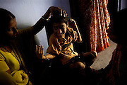 Suraj, 7, a child born with severe mental and physical disabilities from gas-affected parents, is using a medical chair to sit straight while a volunteer and his mother are playing with him, on the floor of Chingari Trust in Bhopal, Madhya Pradesh. The trust offers assistance, education, physiotherapy and advice to hundreds of children born from gas-affected parents or being fed highly contaminated water since a very early age, when the body is more likely to be affected and to suffer irreparable damage.