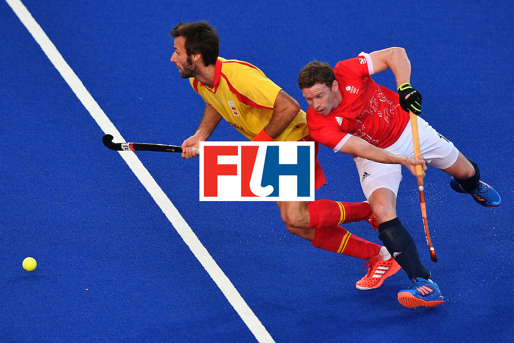 Spain's David Alegre (L) and Great Britain's Michael Hoare vie during the mens's field hockey Britain vs Spain match of the Rio 2016 Olympics Games at the Olympic Hockey Centre in Rio de Janeiro on August, 12 2016. / AFP / Carl DE SOUZA        (Photo credit should read CARL DE SOUZA/AFP/Getty Images)
