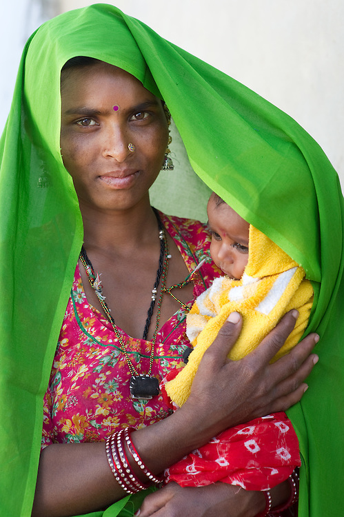 Rajasthani mother from the Bhopa tribe, holding her baby son in her arms. Thar desert, Rajasthan, India.