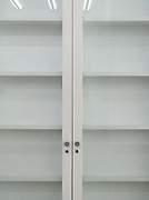 empty bookshelf display closet with glass doors