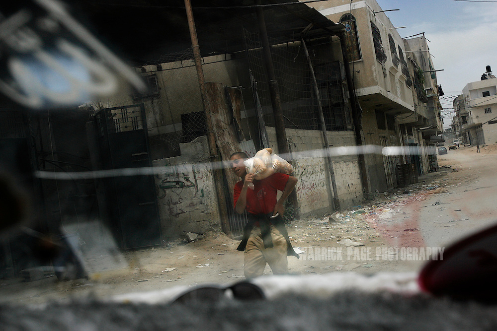 ATATRA, GAZA STRIP - JUNE 4: A Palestinian boy carrying bread is seen through the cracked windshield of a car, June 4, 2009, in Atatra, Gaza Strip. Eight members of the Abu Halima family were killed after a white phosphorus artillery strike burst through the ceiling of their home during the recent war in Gaza, while two others were shot dead while trying to evacuate the wounded. Not since Fallujah or Grozny has white phosphorus been used so extensively in a civilian area. Phosphorus shells are legal to use as a battlefield obscurant in unpopulated areas, but are banned from use under the UN's Convention on Conventional Weapons (CCW) where civilians may be harmed. (Photo by Warrick Page)
