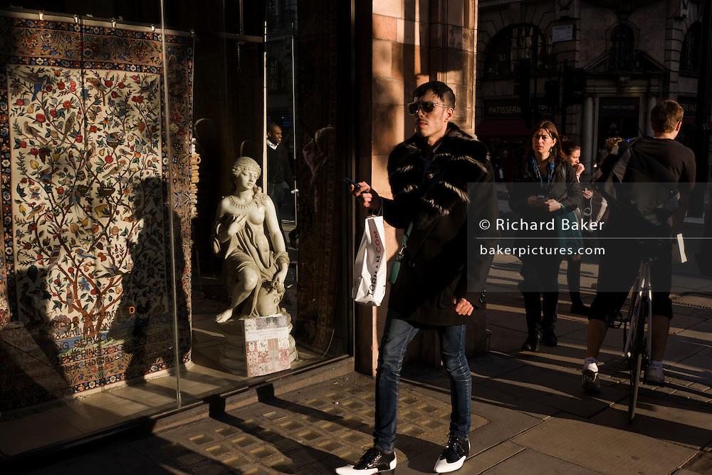 A fashion conscious male with a small girl statue credited to the 19th century Florence-born artist Raffaello Romanelli.