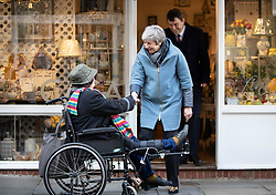 © Licensed to London News Pictures. 04/03/2019. Salisbury, UK. Prime Minister Theresa May talks with shopper in a wheelchair during a visit to Salisbury on the first anniversary of the poisoning of former Russian spy Sergei Skripal and his daughter Yulia in March 2018. They both survived the nerve agent attack but a resident of nearby Amesbury, Dawn Sturgess, died in June 2018 after coming in contact with the poison. Two Russians have been named in connection with the attack. Photo credit: Peter Macdiarmid/LNP