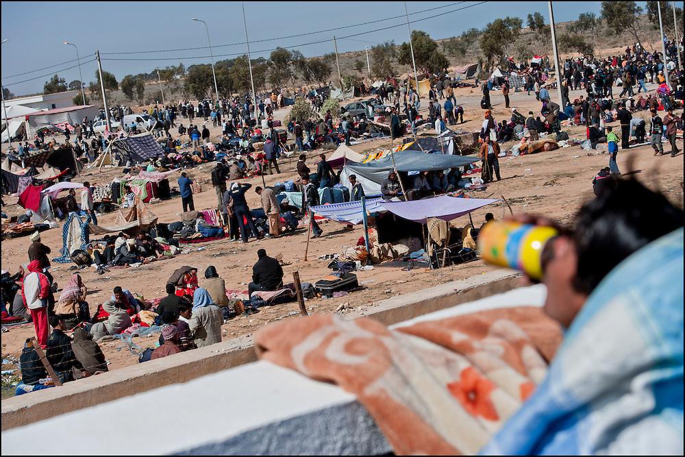 Un réfugié originaire du Bangladesh boit une canette de soda au poste frontière de Ras Jedir après avoir fui la Libye. Plus de 140 000 réfugiés ont déjà quitté la Libye par la Tunisie ou l'Egypte et des milliers continuent d'arriver chaque jours. Jeudi 3 Mars 2011, Ras Jedir, Tunisie. © Benjamin Girette/IP3 press