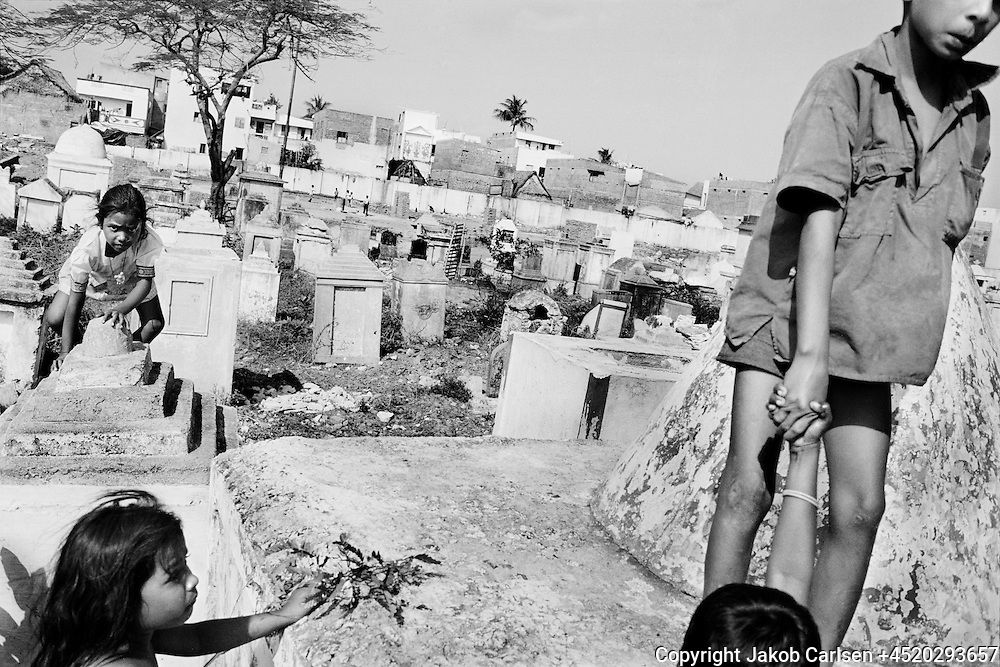 Untouchable children live in the cemetary. They play on and next to graves and tombstones. They will most likely be forced to take over the very badly paid job of burning the dead, because this line of work is considered their duty as untouchables.