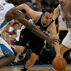 Mar 01, 2010; New Orleans, LA, USA; San Antonio Spurs guard Manu Ginobili (20) drives between New Orleans Hornets center Emeka Okafor (left) and forward Peja Stojakovic (right) during the first half at the New Orleans Arena. Mandatory Credit: Derick E. Hingle-US PRESSWIRE