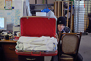 A man in a toque poses with a red suitcase full of clothes in the loading dock of Worth a Second Look, a second hand store in Kitchener, Ontario, Canada. The man is part of Job Cafe, a casual labour program offered by The Working Centre.