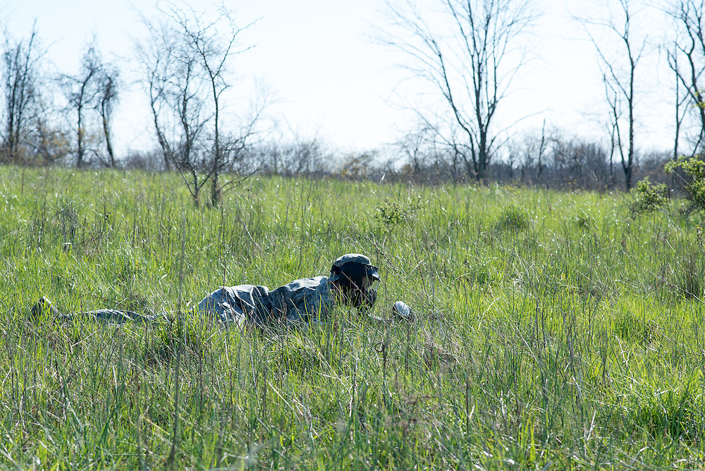 A cadet lays low in the grass after his team comes under fire during their mobile exercise on April 16, 2016. Photo by Ohio University / Kaitlynn Stone