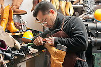 Mature shoemaker concentrating on repairing footwear in workshop