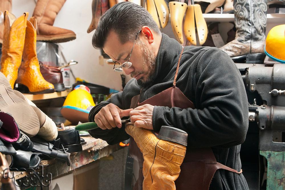 Mature shoemaker concentrating on repairing footwear in workshop