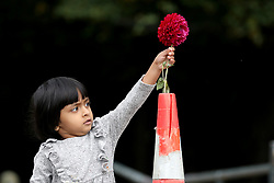 March 17, 2019 - Christchurch, New Zealand - A little girl places a flower as a tribute to victims of the mosque attacks outside the Masjid Al Noor mosque in Christchurch. At least 49 people dead and more than 40 people injured following attacks on two mosques in  Christchurch. The national security threat level has been increased from low to high for the first time in New Zealand's history after this attack. (Credit Image: © Sanka Vidanagama/NurPhoto via ZUMA Press)