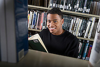 Male University student reading in library, portrait