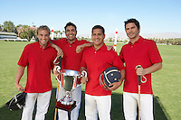 Smiling Polo Players standing on polo field holding equipment and trophy
