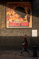 © Licensed to London News Pictures. 18/10/2018. LONDON, UK. A woman walks by a new artwork in Brick Lane. The artwork features human rights activist Mala Sen and is one of 20 newly-commissioned artworks, designed by the London Tate Collective team, Tate's group for 16 to 25 year old artists, which will appear in public spaces across the city marking the centenary of women's suffrage.  Called LDN WMN, the artworks celebrate women who have played a crucial role in London's history, but have been largely overlooked.  Photo credit: Stephen Chung/LNP