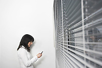Female office worker using mobile phone in front of office window side view