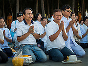 """02 JANUARY 2016 - KHLONG LUANG, PATHUM THANI, THAILAND: Men pray at Wat Phra Dhammakaya on the first day of the 5th annual Dhammachai Dhutanaga (a dhutanga is a """"wandering"""" and translated as pilgrimage). More than 1,300 monks are participating pilgrimage through central Thailand. The purpose of the pilgrimage is to pay homage to the Buddha, preserve Buddhist culture, welcome the new year, and """"develop virtuous Buddhist youth leaders."""" Wat Phra Dhammakaya is the largest Buddhist temple in Thailand and the center of the Dhammakaya movement, a Buddhist sect founded in the 1970s. The monks are using busses on some parts of the pilgrimage this year after complaints about traffic jams caused by the monks walking along main highways.          PHOTO BY JACK KURTZ"""