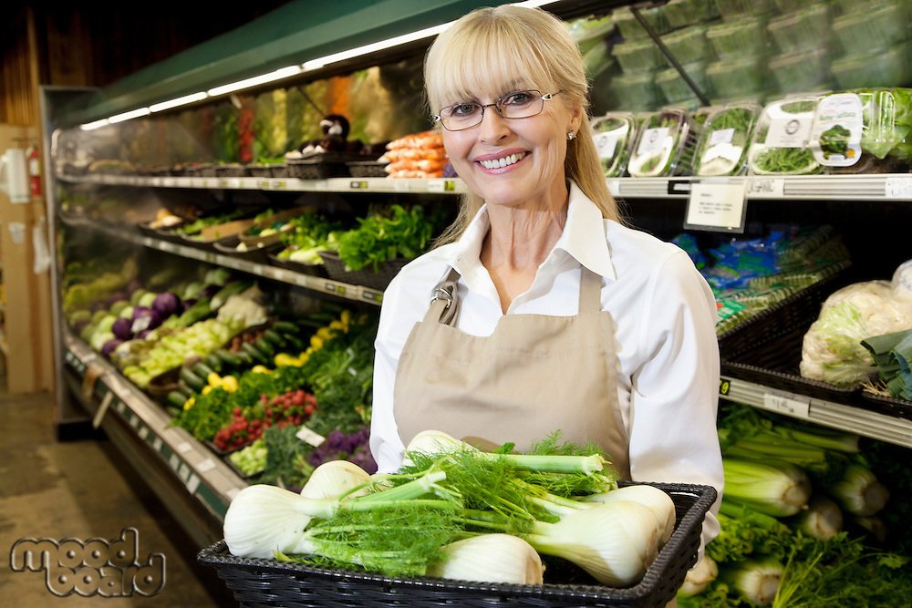 Portrait of a happy senior woman carrying bok choy in vegetable market