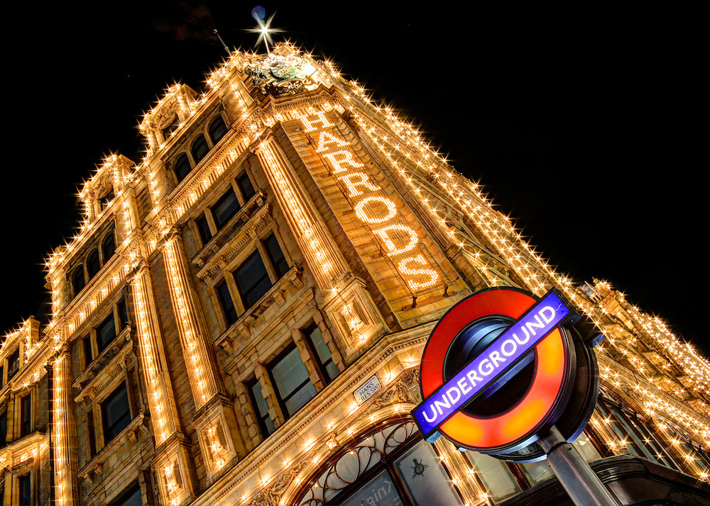 The iconic London underground sign outside Harrods in London. Harrods is brightly illuminated by thousands of light bulbs