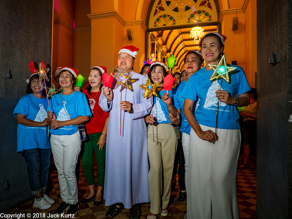 """23 DECEMBER 2018 - CHANTABURI, THAILAND: The Christmas procession leaves the church at the Cathedral of the Immaculate Conception's Christmas Fair in Chantaburi. Cathedral of the Immaculate Conception is holding its annual Christmas festival, this year called """"Sweet Christmas @ Chantaburi 2018"""". The Cathedral is the largest Catholic church in Thailand and was founded more than 300 years ago by Vietnamese Catholics who settled in Thailand, then Siam.   PHOTO BY JACK KURTZ"""