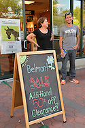 Garden City, New York, U.S. - June 6, 2014 -  ANTHONY RANDOLPHI of Valley Stream, on staff at New York Running Co, is by a chalkboard easel sign announcing the store's Belmont Sale, during the Garden City Belmont Stakes Festival, celebrating the 146th running of Belmont Stakes at nearby Elmont the next day. There was street festival family fun with live bands, food, pony rides and more, and a main sponsor of this Long Island night event was The New York Racing Association Inc.