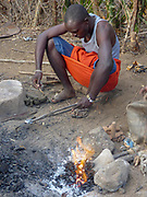 heating an iron nugget in an open furnace. Gidonwoduk tribe, the former Datoga blacksmith tribe. Today they are a separate tribe. They do not marry with Datoga since they discovered the secrets of blacksmithing. Photographed in Africa, Tanzania, Lake Eyasi