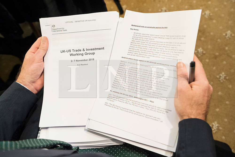 """© Licensed to London News Pictures. 27/11/2019. London, UK. A journalist holds revealing official government documents showing the US is demanding that the NHS will be """"on the table"""" in talks on a post-Brexit trade deal on the National Health Service. Photo credit: Ray Tang/LNP"""