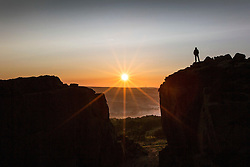 © Licensed to London News Pictures. 24/05/2016. Ilkley UK. Picture shows a man standing on top of the cow & Calf rocks at Ilkley Moor watching this morning's sunrise in Yorkshire. Photo credit: Andrew McCaren/LNP