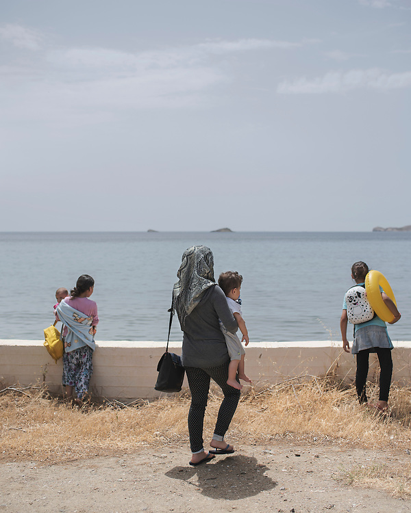 Syrian refugee women and children looking out to sea at Gourna Beach. It is the first time they have been back to the sea since they were rescued by the coast guard after crossing from Turkey.