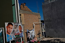"Workmen construct a chapel next to a sign with a picture of a recently deceased youth in  the cematary in Culiacan, Mexico, known localls as the ""Pantheon"".  Some of the chapels, where the dead are buried, are two-story buildings complete with electricity and air conditioning. This phenomenon, where people build increasingly large, luxurious memorials to their dead family members, is often associated with Mexico's Narco Culture."