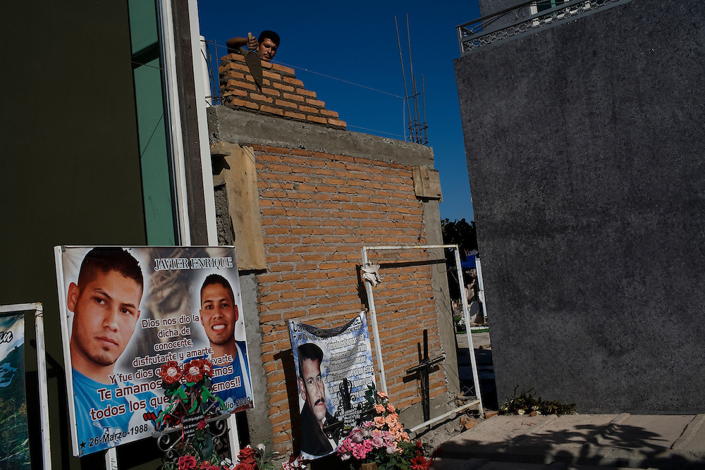 """Workmen construct a chapel next to a sign with a picture of a recently deceased youth in  the cematary in Culiacan, Mexico, known localls as the """"Pantheon"""".  Some of the chapels, where the dead are buried, are two-story buildings complete with electricity and air conditioning. This phenomenon, where people build increasingly large, luxurious memorials to their dead family members, is often associated with Mexico's Narco Culture."""