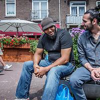 Nederland, Amsterdam, 23 juli 2016.<br />We volgen de Syrische jongen Ibrahim Najjar in de Spaarndammerbuurt in zijn zoektocht naar de ingredienten voor het Syrische kipgerecht Mskhan, een Syrisch ovengerecht met kip, citroen en ui.<br />Hij heeft zijn buren uitgenodigd bij hem te komen eten.<br />Op de foto: Ibrahim begroet en praat met een buurtbewoner.<br /> <br /> <br /> <br /> Foto: Jean-Pierre Jans
