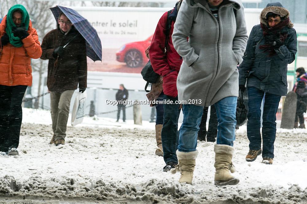 Brussel 12 maart 2013. Zware sneeuwbuien teisteren geheel Belgie. De langste files sinds tijden. Het verkeer, bussen, treinen hebben veel last van de sneeuw.De sneeuw wordt al snel drap, door het zout en het verkeer.Voetgangers zetten zich schrap.