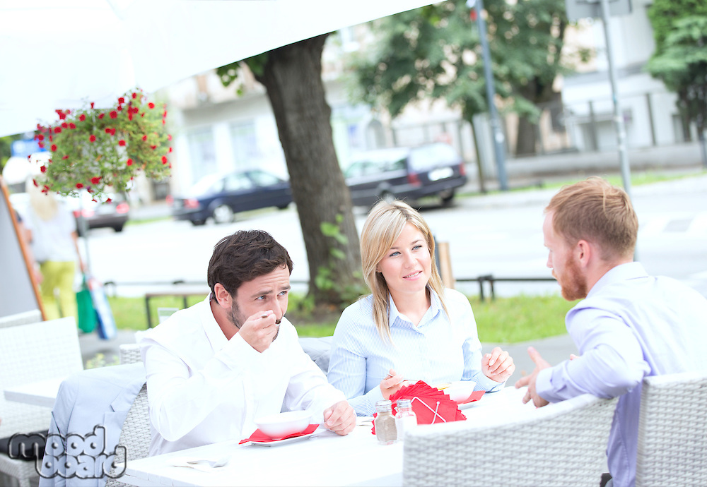 Businesspeople having food at outdoor restaurant