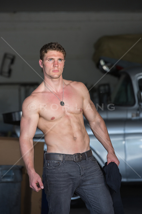 shirtless muscular man in an auto repair shop