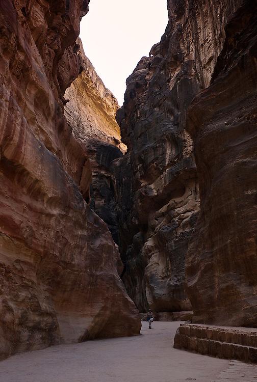 Le sîq, entrée principale à la ville antique de Petra, est un défilé étroit (3m au point le plus étroit) et sinueux, long de 1500 mètres. Ses parois ont entre 90 et 200 mètres de hauteur. Les personnages dans la photo donnent l'échelle. .Main entrance to the anfient city of Petra, the siq is a narrow canyon that is approximately 1500 meters long. The enclosing walls are 90 to 200m tall. The people in the picture give the scale. .Der Siq ist eine etwa 1,5 km lange Schlucht, die zwischen 90 und 200m tief ist und als Haupteingang zur antiken Stadt Petra dient. Die Menschen im Bild geben den Maßstab.