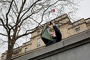 A tourist takes a picture beneath Canada House, in Trafalgar Square, on 29th March, 2018 in London, England.