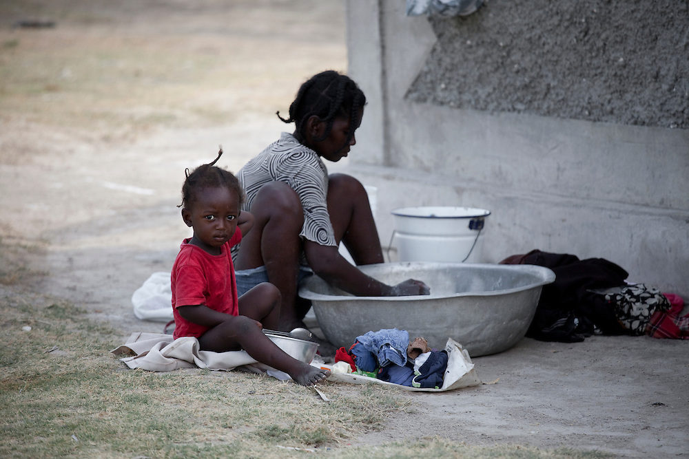 A young girl looks toward the camera as her mother washes clothes on Ile de La Gonave, Haiti