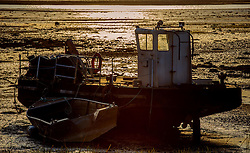 A barge sits in the Cromarty Firth Scotland grounded by a low tide bathed in light from the setting sun<br /> <br /> (c) Andrew Wilson | Edinburgh Elite media