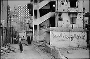 """Beirut, Lebanon July 1982. Near by the """"Cite sportive"""" west Beirut.  A man carrying water containers goes back to his home in this heavily shelled area of the city. ©Herve Merliac"""