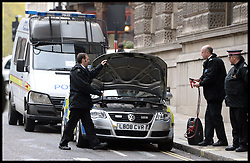 Police officers jump start a Police car outside The Old Bailey, London, United Kingdom. Monday, 18th November 2013. Picture by Andrew Parsons / i-Images