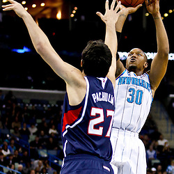 December 26, 2010; New Orleans, LA, USA; New Orleans Hornets power forward David West (30) shoots over Atlanta Hawks center Zaza Pachulia (27) during the first quarter at the New Orleans Arena.  Mandatory Credit: Derick E. Hingle