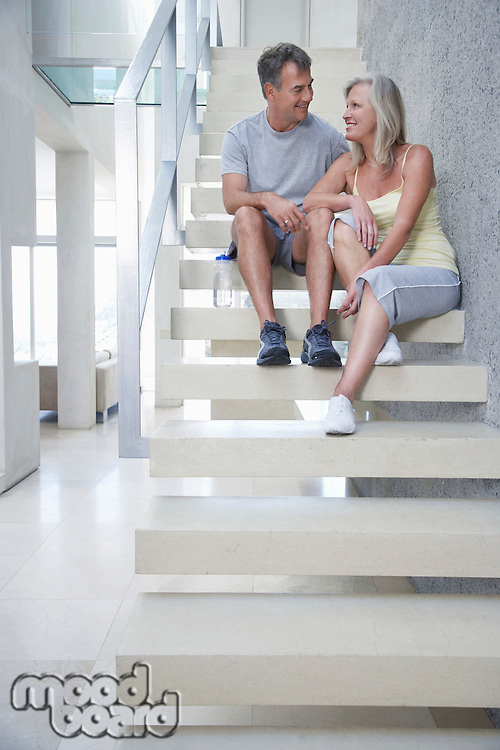 Mature couple sitting on stairs before exercise looking in eyes