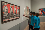 Raise high the banner of Marx Engel, Lenin and Stalin, 1933 by Gustave Klutsis - Pupils from Thomas Tallis School in Kidbrooke who are doing Russian studies, visit the exhibition - Tate Modern's new exhibition Red Star Over Russia on the 100th anniversary of the October Revolution. The exhibition offers a visual history of the Soviet Union, revealing how seismic political events inspired a wave of innovation in art and graphic design. Featuring over 250 posters, paintings and photographs, many on public display for the first time, the exhibition will provide a chance to understand how life and art were transformed during a defining period in modern world history.