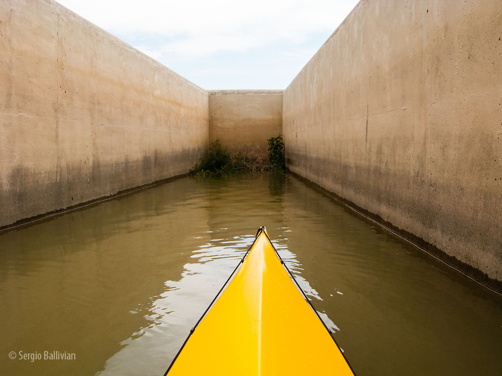 The bow of a yellow TRAK folding sea kayak sits in a dead-end urban waterway at the Boulder Reservoir in Boulder, Colorado.