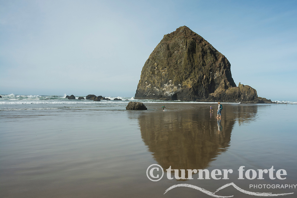 Mother and two children run on the seashore and in the reflection of Haystack Rock, Cannon Beach, Oregon.