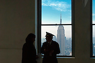FEB. 27, 2011 - MANHATTAN: View of Empire State Building early morning through indoor window of 30 Rockefeller Center at least 66 floors up, with Guard with visitor silhouetted by window with beautiful sky, in Manhattan, New York City, New York, USA,