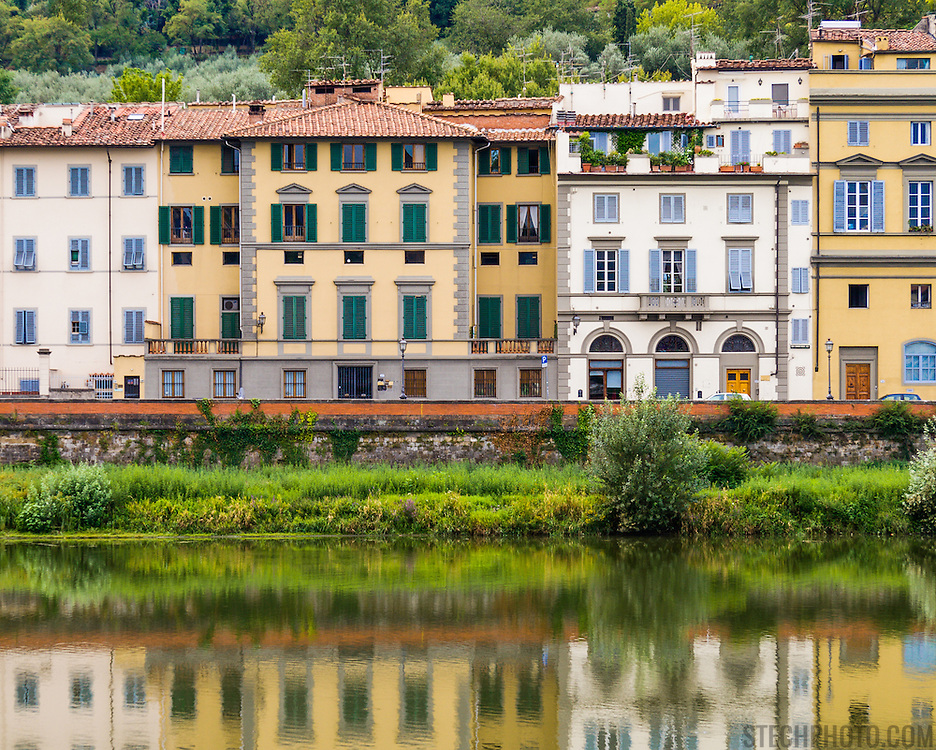A row of residential apartment buildings along the riverbank of the Arno River in Florence, Italy.