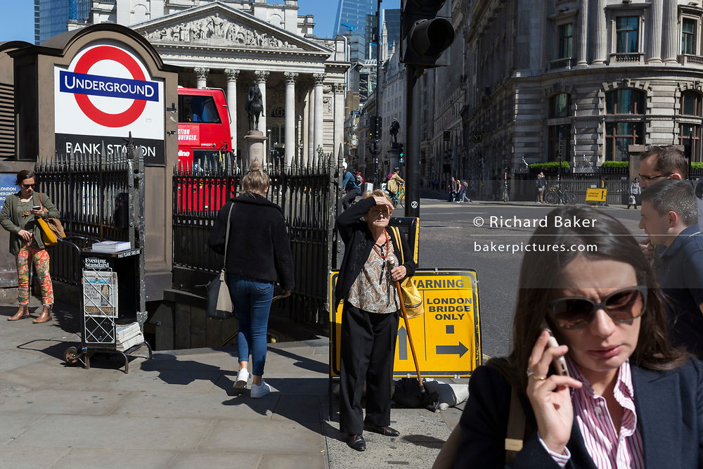 Surrounded by other Londoners, an elderly lady shields her face outside one entrance of Bank Underground Station in the City of London, the capital's ancient, financial district, on 14th May, in London, England. (Photo by Richard Baker / In Pictures via Getty Images)